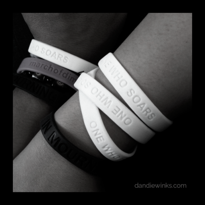 We wear white One Who Soars and black In Mourning wristbands